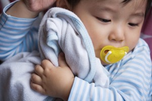 Baby Holding Blanket --- Image by © Ken Seet/Corbis
